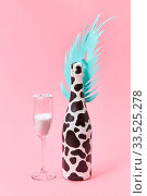 Holiday decorative composition of painted champagne bottle with black spots and paper cut tropical leaf with glass of white powder on a pastel millennial pink background, copy space. Holiday card. Стоковое фото, фотограф Zoonar.com/Iaroslav Danylchenko phoographer / easy Fotostock / Фотобанк Лори