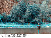 The fisherman stands in the water and catches fish in a mountain river against the background of a rock covered with forest. Стоковое фото, фотограф Акиньшин Владимир / Фотобанк Лори