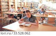 Купить «Schoolchildren preparing for lesson in school library, reading textbooks», видеоролик № 33528062, снято 27 мая 2020 г. (c) Яков Филимонов / Фотобанк Лори