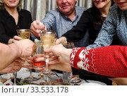 Люди за праздничным столом стукаются бокалами с шампанским и водкой. Фокус на бокалах (2020 год). Редакционное фото, фотограф Игорь Низов / Фотобанк Лори