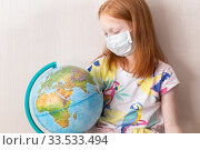 Купить «Adorable red haired girl wearing medicine mask for stop coronavirus outbreak with globe. Self isolation at home. Coronavirus worldwide concept. Vertical photo», фото № 33533494, снято 10 апреля 2020 г. (c) Evgenia Shevardina / Фотобанк Лори