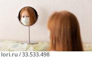Купить «Adorable red haired girl wearing medicine mask for stop coronavirus outbreak. Girl looks at herself at mirror. Self isolation at home», фото № 33533498, снято 10 апреля 2020 г. (c) Evgenia Shevardina / Фотобанк Лори