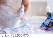 Купить «Inattentive husband burning clothing while ironing», фото № 33535070, снято 19 декабря 2017 г. (c) Elnur / Фотобанк Лори