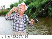 Fisherman changing bait on hook. Стоковое фото, фотограф Яков Филимонов / Фотобанк Лори
