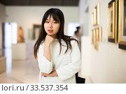 Купить «Serious chinese female visitor looking at artwork painting in museum», фото № 33537354, снято 6 июля 2020 г. (c) Яков Филимонов / Фотобанк Лори