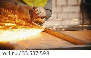 Man worker grinding the seams of an iron frame in the workshop. Стоковое видео, видеограф Константин Шишкин / Фотобанк Лори