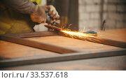 Купить «Man worker grinding the seams of a metal frame in the workshop», видеоролик № 33537618, снято 5 июня 2020 г. (c) Константин Шишкин / Фотобанк Лори