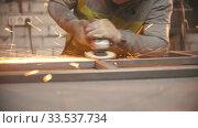 Купить «Grinding the seams of an iron frame in the welding workshop», видеоролик № 33537734, снято 29 мая 2020 г. (c) Константин Шишкин / Фотобанк Лори