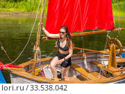 Russia, Samara, July 2019. Lovely girl on a wooden boat with a red sail on a summer sunny day. Редакционное фото, фотограф Акиньшин Владимир / Фотобанк Лори