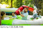 Купить «Team of friends playing with inflatable sticks on the trampoline», фото № 33538198, снято 5 августа 2020 г. (c) Яков Филимонов / Фотобанк Лори