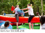 Купить «Women fighting by pillows on inflatable beam», фото № 33538218, снято 14 июля 2020 г. (c) Яков Филимонов / Фотобанк Лори