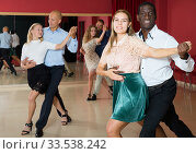 Positive adult pairs enjoying dancing salsa in modern dance studio. Стоковое фото, фотограф Яков Филимонов / Фотобанк Лори