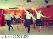 Young people practicing twist movements together at modern dance studio. Стоковое фото, фотограф Яков Филимонов / Фотобанк Лори