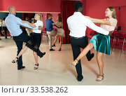 Young positive people dancing vigorous jive movements in dance studio. Стоковое фото, фотограф Яков Филимонов / Фотобанк Лори