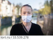 Купить «COVID-19 pandemic coronavirus. Young girl in city street wearing face mask protective for spreading of coronavirus disease 2020. Close up of young woman with medical mask on face against SARS-CoV-2», фото № 33539278, снято 8 апреля 2020 г. (c) Matej Kastelic / Фотобанк Лори