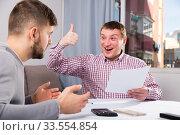 Купить «Satisfied man with partner working with documents at home», фото № 33554854, снято 7 февраля 2018 г. (c) Яков Филимонов / Фотобанк Лори