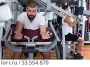 Man on power exercise machine in gym. Стоковое фото, фотограф Яков Филимонов / Фотобанк Лори