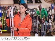 Купить «Girl choosing alpine ski in sport goods store», фото № 33555054, снято 16 апреля 2019 г. (c) Яков Филимонов / Фотобанк Лори