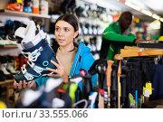 Young female skier looking for modern ski boots in sport goods store. Стоковое фото, фотограф Яков Филимонов / Фотобанк Лори