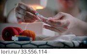 Купить «Young woman designer putting pins in the holder indoors», видеоролик № 33556114, снято 4 июля 2020 г. (c) Константин Шишкин / Фотобанк Лори