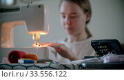 Купить «Young woman designer sewing a white protective reusable mask using a sewing machine», видеоролик № 33556122, снято 4 июля 2020 г. (c) Константин Шишкин / Фотобанк Лори