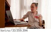 Купить «Woman working on a laptop with a glass of wine», видеоролик № 33559394, снято 13 апреля 2020 г. (c) Ekaterina Demidova / Фотобанк Лори