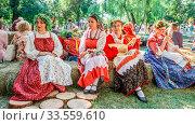 Russia Samara August 2019: Flower Festival. Girls in national Russian costumes are sitting on straw bundles. Редакционное фото, фотограф Акиньшин Владимир / Фотобанк Лори
