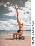 Купить «Beautiful woman doing a headstand on the beach on a summer sunny day.», фото № 33559626, снято 7 июля 2019 г. (c) Акиньшин Владимир / Фотобанк Лори