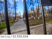 Купить «Центральный парк закрыт для посетителей из-за эпидемии коронавируса, г. Королев, Россия. Вид на парк сквозь закрытую решетку ворот.», фото № 33559934, снято 15 апреля 2020 г. (c) chaoss / Фотобанк Лори