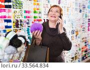 Купить «Woman with needlework accessories and talking on phone», фото № 33564834, снято 10 мая 2017 г. (c) Яков Филимонов / Фотобанк Лори