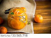 Купить «tangerine jam in a glass jar on a wooden table», фото № 33565718, снято 16 апреля 2020 г. (c) Peredniankina / Фотобанк Лори