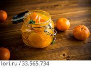 Купить «tangerine jam in a glass jar on a wooden table», фото № 33565734, снято 16 апреля 2020 г. (c) Peredniankina / Фотобанк Лори