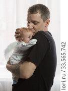 Молодой папа с нежностью держит маленькую дочку. У младенца крылья ангела. Стоковое фото, фотограф Наталья Гармашева / Фотобанк Лори