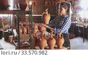 Купить «Young woman potter putting in order crafts in pottery studio», видеоролик № 33570982, снято 4 августа 2020 г. (c) Яков Филимонов / Фотобанк Лори