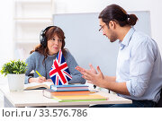Купить «Young female student and male english teacher in the classroom», фото № 33576786, снято 27 ноября 2019 г. (c) Elnur / Фотобанк Лори
