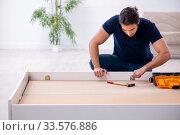 Купить «Young male contractor installing furniture at home», фото № 33576886, снято 11 ноября 2019 г. (c) Elnur / Фотобанк Лори