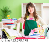Купить «Young woman ironing clothing at home», фото № 33579178, снято 29 мая 2018 г. (c) Elnur / Фотобанк Лори