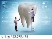 Doctors examining giant tooth in dental concept. Стоковое фото, фотограф Elnur / Фотобанк Лори