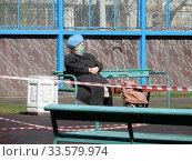 Пожилая женщина в медицинской маске отдыхает на лавочке в дни самоизоляции при коронавирусе COVID-19. Хабаровская улица. Район Гольяново. Город Москва. Россия (2020 год). Редакционное фото, фотограф lana1501 / Фотобанк Лори