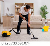 Man cleaning home with vacuum cleaner. Стоковое фото, фотограф Elnur / Фотобанк Лори
