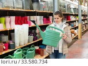 Купить «Woman buys watering can in store for gardeners», фото № 33580734, снято 7 июня 2020 г. (c) Яков Филимонов / Фотобанк Лори