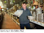 Puzzled man choosing wickerwork in shop. Стоковое фото, фотограф Яков Филимонов / Фотобанк Лори