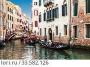 Gondolas with tourists sailing along a canal in Venice, Italy (2017 год). Редакционное фото, фотограф Наталья Волкова / Фотобанк Лори