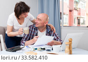 Man working with financial documents at laptop, woman offering coffee. Стоковое фото, фотограф Яков Филимонов / Фотобанк Лори