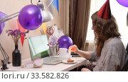 Купить «Woman celebrating birthday from home», видеоролик № 33582826, снято 19 апреля 2020 г. (c) Сергей Петерман / Фотобанк Лори