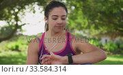 Купить «Woman looking at her watch in a park», видеоролик № 33584314, снято 9 апреля 2019 г. (c) Wavebreak Media / Фотобанк Лори