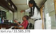 Купить «African man adding hair extensions», видеоролик № 33585378, снято 19 сентября 2019 г. (c) Wavebreak Media / Фотобанк Лори