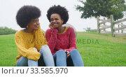 Купить «Two mixed race women laughing in park», видеоролик № 33585970, снято 17 мая 2019 г. (c) Wavebreak Media / Фотобанк Лори