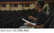 Купить «Caucasian high school teenage boy in the auditorium preparing for a performance», видеоролик № 33586462, снято 18 сентября 2019 г. (c) Wavebreak Media / Фотобанк Лори