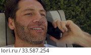 Young man talking at the phone. Стоковое видео, агентство Wavebreak Media / Фотобанк Лори